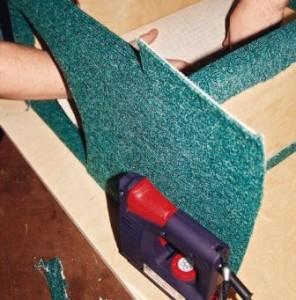 Степлером обтяните домик ковролином снаружи и изнутри. После этого привинтите его к основной конструкции шуруповертом