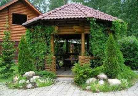 Садовая беседка должна по стилю сочетаться с загородным домом, однако, вы можете её тщательно замаскировать растениями