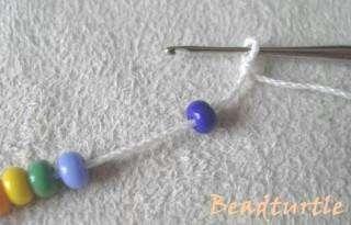 Далее необходимо произвести захват нити непосредственно за первой бисеринкой и протянуть ее в только что сделанную первую петлю