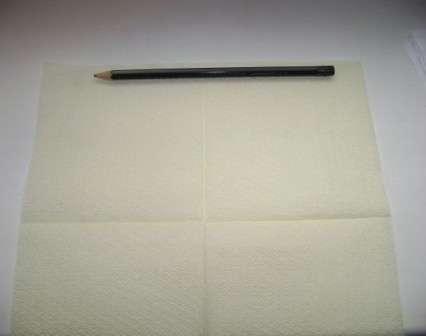 Полностью разверните одну салфетку и у верхнего её края положите карандаш. Лучше всего, если карандаш длиннее салфетки, так как тогда будет проще её закручивать.
