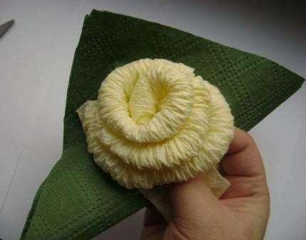 После этого возьмите салфетки зелёного цвета, чтоб сделать листочки цветка.</p> <p> Сложите салфетки треугольником и заверните его у основания бутона.</p> <p> Должен получиться листик. Сделайте три таких листочка для одной розы.» width=»429″ height=»336″/></p></div> </p> <p>Снизу закрепите салфетки ниткой, чтоб они не распадались. Можете также проклеить розу клеем.</p> <p> Цветок готов и его можно вставить в стаканчик.</p> <p> Если вы закрепите салфетки на проволоке, то роза поместится в высокую вазу.</p> <p><div style=