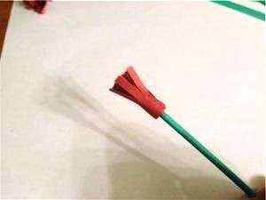 После этого начните наматывать на стебель полоски красной бумаги. Когда вся полоска намотана на стебель, закрепите её клеем, дождитесь высыхания и потом начните расправлять бутон.