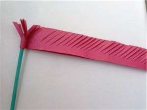 Из цветной бумаги зелёного цвета сделайте стебель для гвоздики. Чтобы он был плотным, обворачивайте в бумагу зубочистки и проклеивайте клеем.