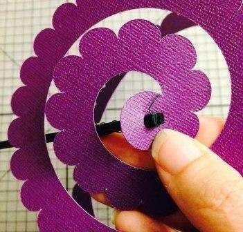 Когда палочка готова, воткните её в центр спирали. После этого палочку вытягивайте и отдельно скрутите спираль в цветок. Когда закончите, снова воткните палочку, а бумажные лепестки зафиксируйте клеем.