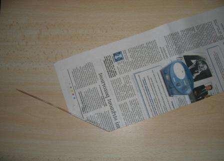 Вокруг вязальной спицы или проволоки обворачиваем полосы так, чтобы спица лежала наискось касательно газеты