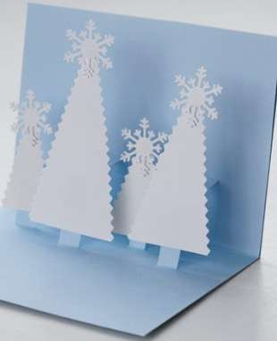 Вклеенные вовнутрь открытки елочки можно украсить плоскими украшениями из той же бумаги.