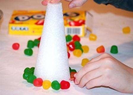 Начинайте заполнять пенопласт разноцветным мармеладом с нижнего края