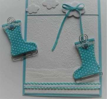 С помощью тесьмы или ленты соедините ботинки между собой и приклейте к облачку в верхней части открытки. Всю открытку вы можете задекорировать пуговичками, которые будут гармонировать по цветовой гамме со всей аппликацией.