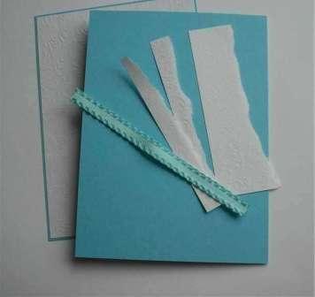 Из плотной бумаги бирюзового цвета вырежьте прямоугольник размерами 14×18 см. Сложите эту бумагу ровно пополам. После этого из белой бумаги вырежьте прямоугольник меньшего размера - 13×17 см. При помощи двустороннего скотча склейте эти два листа бумаги между собой. После этого аккуратно обрежьте края бирюзовой бумаги, чтобы они выступали не более чем на 0,5 см