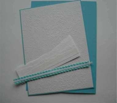 Чтобы сделать сугробы, вам нужно будет просто оторвать несколько полосок белой бумаги. Приклейте сугробы на подготовленную основу для открытки. Возьмите голубую атласную ленту и к ней пришейте белую тесьму. Данный элемент декора приклейте при помощи клеевого пистолета к нижней части открытки.