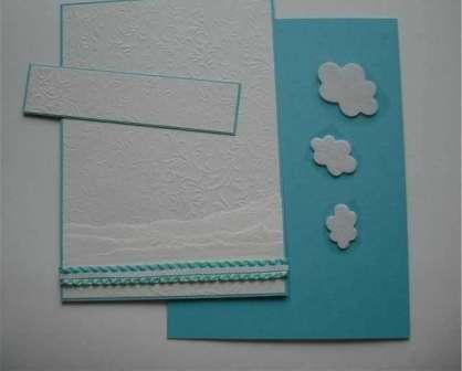 Вырежьте прямоугольник из бирюзовой бумаги шириной 13,5×2,5 см, а также прямоугольник из белой бумаги шириной 13×2,5 см. Эту деталь вам нужно будет расположить в верхней части открытки. Из белого фетра вырежьте облака и приклейте их к этому прямоугольнику.