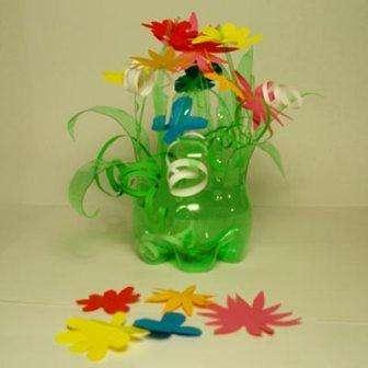 Один из простых способов сделать вазу из бутылок – обрезать горлышко и часть бутылки нарезать одинаковыми полосами.