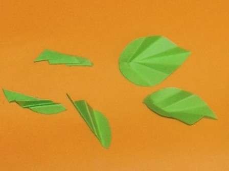 После этого приступите к изготовлению листочков. Для этого вам понадобится цветная бумага зеленого цвета. Вырежьте листочек, а потом сложите его гармошкой, для придания рельефной структуры.