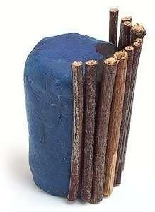 Теперь можете приступить к изготовлению горшочка. Для этого вам понадобится большой кусок пластилина, из которого вы должны будете скатать цилиндр. Чтобы украсить горшочек, возьмите ровные палочки. Использовать можно даже деревянные шпажки, если вы не нашли достаточное количество сухих веточек без изгибов.
