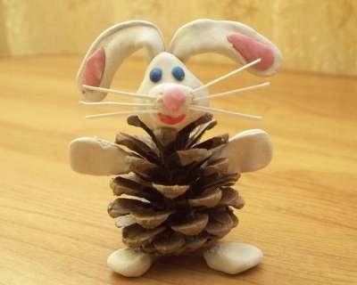 Из шишек и пластилина может получиться весёлый зайчик.