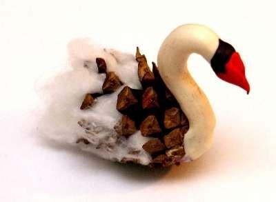 Используя сосновую шишку, пластилин и вату, получится весьма изящный лебедь.
