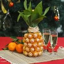 Места стыка листьев и конфет можно задекорировать с помощью бечевки. Ваш ананас готов.