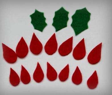 Нарисуйте семь больших и семь маленьких капелек, а также три разных по размеру детали для листьев зеленого цвета. После этого вырежьте все эти заготовки из красного и зеленого фетра.