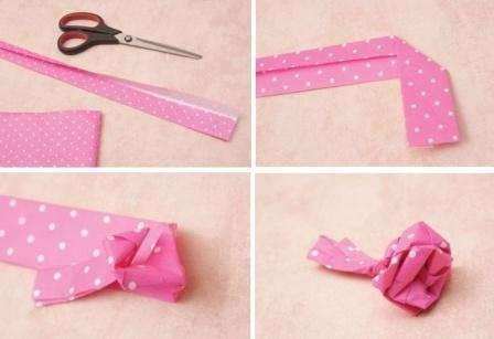 Возьмем оберточную бумагу, цвет выберите по желанию, например, розовый в белый горошек. Нарезаем неширокими, по 8 см полосками. Чем длиннее, тем розочка получится более пышной. Загибаем края вовнутрь, конец полоски загибаем под 90 градусов, образую букву «Г». Удерживая за хвостик, загибаем полоску по кругу, капелькой клея фиксируем получившийся бутон.