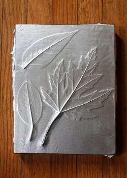 Теперь клеем намажьте снова листья и приложите фольгу.</p> <p> Заранее отрежьте большой кусок фольги, чтобы ее хватило на всю основу. Красиво задекорируйте фольгу, чтобы она плотно прилегала к деревянной основе.» width=»250″ height=»350″/></p></div> </p> <p>Возьмите черную краску в баллончике и нанесите сверху фольги. После высыхания краски можно приступить к созданию оттенков.</p> <p> Для этого скребком начните стирать краску. Старайтесь не повреждать саму фольгу, но при этом сильно не переживайте, все исправить можно с помощью черного фломастера или маркера.</p> <p> Осеннее панно своими руками готово.</p> <p><div style=