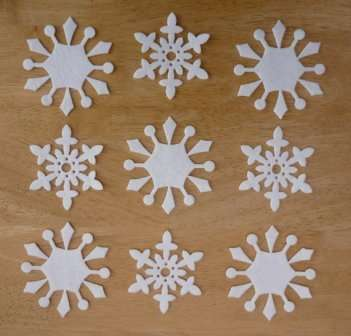 Для того чтобы снежинка получилась красивой, вам нужно будет вспомнить азы геометрии или черчения. Возьмите циркуль и начертите два круга на фетре красного и белого цвета. Можете выбрать любые цветовые решения для своих снежинок, например, сочетания синего и белого, розового и белого или золотого.
