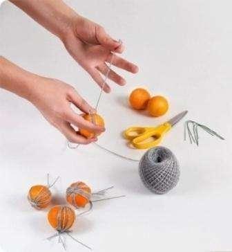 Свободное пространство между мандаринками можно заполнить веточками или искусственными листьями.