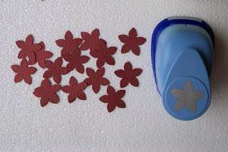 Берем в руки дырокол «цветочком» и из картона цвета бордо и с его помощью вырубаем цветочки, в количестве 18 шт