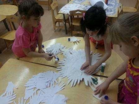 Теперь можете приступить к приклеиванию ладошек. Удобнее всего это делать с помощью клея-карандаша или ПВА. Пусть дети самостоятельно приклеивают ладошки по кругу основы для снеговика. Из цветной бумаги вырежьте детали для глазок и нос.