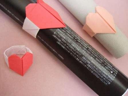 Если вы правильно согнёте все детали, то в центральной части колечка у вас получится красивое сердечко. Оставшуюся бумагу нужно будет согнуть по линиям и затем вставить концы полоски друг в друга.