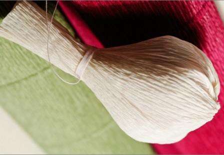 Затем начинайте прикреплять лепесточки и завязывайте их ниткой. В результате конфета у вас должна оказаться внутри лепестков из гофрированной бумаги.