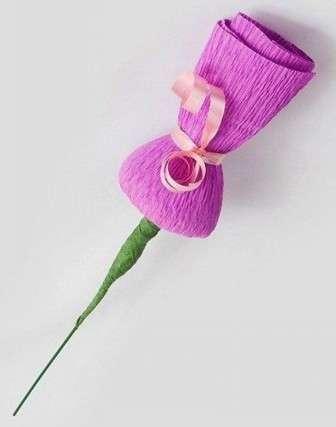 Цилиндр сверху обвяжите розовой лентой. Также необходимо сразу нарезать ленту зелёного цвета тонкими и длинными полосками для того, чтобы далее создать листочки для цветка. Эти полоски следует закрутить в красивые кудряшки используя для этого ножницы.