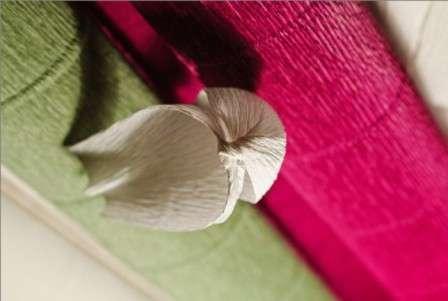 С помощью тейп-ленты присоедините лепестки к стеблю. Цветочек из конфет и гофрированной бумаги готов.