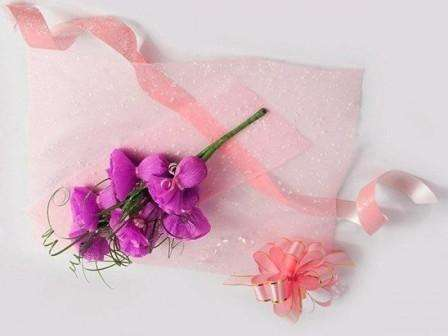 Заверните букет плёнкой, завяжите широкой ленточкой розового цвета и прикрепите бант.