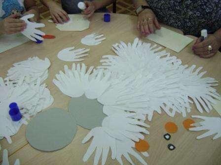 Дошкольники средней и старшей групп могут самостоятельно обвести свои ладошки на листах бумаги. После этого придётся вырезать каждую ладошку. Чтобы сделать снеговика вам нужно будет подготовить не только бумажные ладошки, но и три круга, на которые будете приклеивать детали. Круги должны быть вырезаны из картона, желательно сделать цельную заготовку для снеговика или склеить три круга разного диаметра между собой.