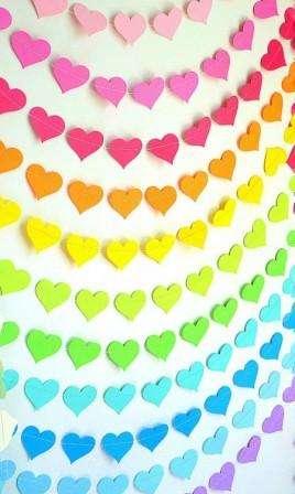 Достаточно быстро можно сделать гирлянду, если нарезать много цветных сердечек, а потом просто пристрочить их друг к другу на швейной машинке.