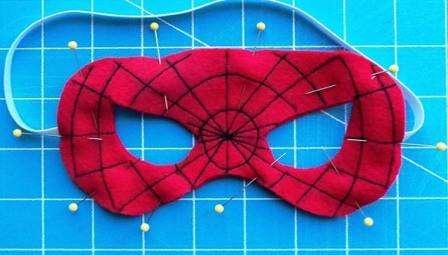 Закрепите две детали маски швейными иголками и прострочите их по контуру. Осталось пришить ленту или бельевую резинку, чтобы маска Человека-Паука не спадала с ребенка.