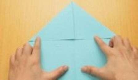 Положив вертикально лист перед собой, загните две его верхние стороны к центру листа