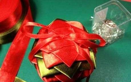 Задекорировать оставшуюся часть шарика нужно с помощью квадратика из ленты. Чтобы шарик можно быть подвесить, прикрепите к нему тоненькую ленточку. Шар из атласных лент готов.
