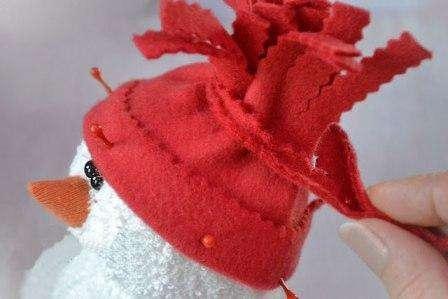 Одеваем снеговика в шапочку, загибаем вверх нижнюю фигурную часть шапки