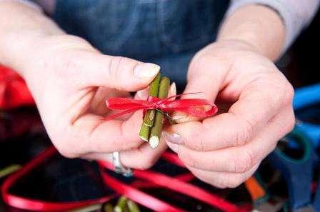 Чтобы придать палочками красивый внешний вид, используйте ленту, которая закроет проволоку. Конец проволоки немного обрежьте и потом воткните палочки в оазис сверху листьев.