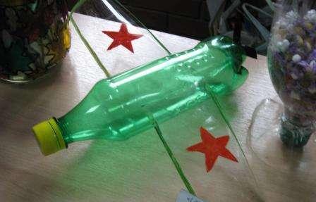 Для того чтобы соорудить самолет с крыльями, сделайте пару надрезов по бокам бутылки и вставьте туда заранее изготовленные крылья.