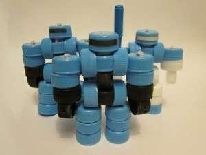 Если вы собрали много пластиковых крышек, то и них получатся оригинальные роботы. Если вставлять между крышками металлические стержни, то поделка будет подвижной. Склеиваются хорошо крышки также клеевым пистолетом.