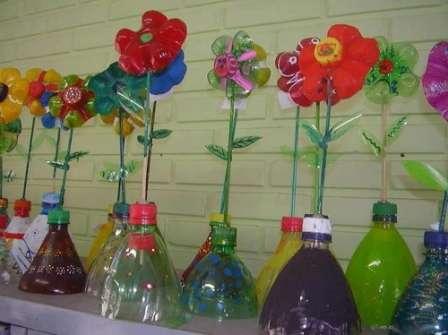 Самый простой вариант – сделать цветок из донышка бутылки. Для этого подойдут бутылки от любых напитков. Отрежьте дно от бутылки и разукрасьте его на свой вкус. Из деревянной шпажки можно сделать стебель