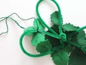 Вырезаем фигурными ножничками зелёные листочки из фетра зелёного цвета, пришиваем их к проволоке