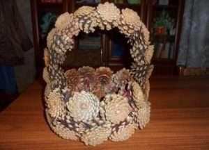 Начитают плетение корзины из шишек с основания. Возьмите тонкую проволоку и соединяйте с ее помощью между собой шишки. Для основания понадобится около 10 шишек. Обворачивайте шишки проволокой до тех пор, пока не сомкнется кольцо.