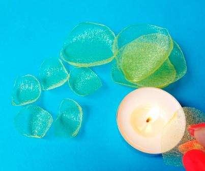 Края будущих лепестков подпиливаем свечкой. Движения нужно проводить быстро над пламенем свечи.