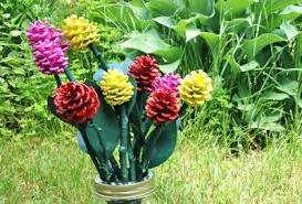 Красиво будет смотреться букет цветов из шишек. Для этого шишки тоже нужно покрасить и потом закрепить на подготовленные стебли.