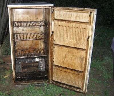 Старый холодильник можно использовать и для холодного копчения. Для этого подготовленный как описано корпус холодильника помещают на возвышении, просверливают отверстие в днище и по